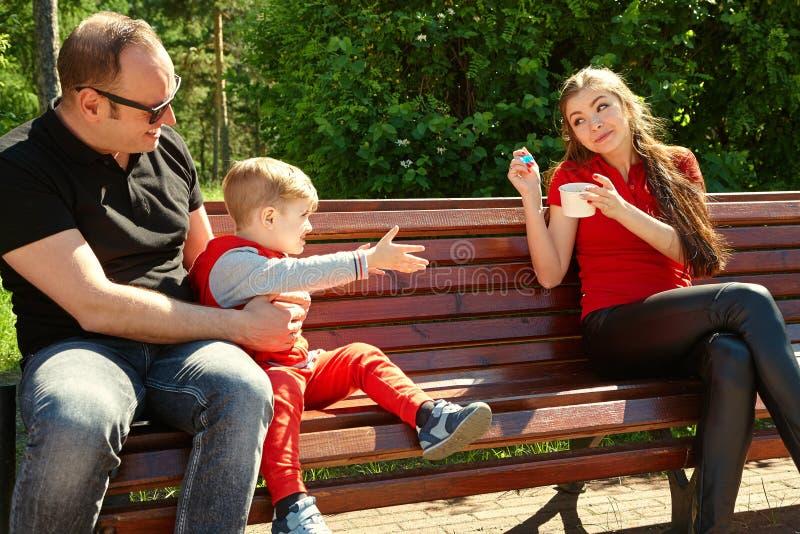 Openluchtportret van een gelukkige familie Mamma, papa en kind die roomijs eten royalty-vrije stock foto's
