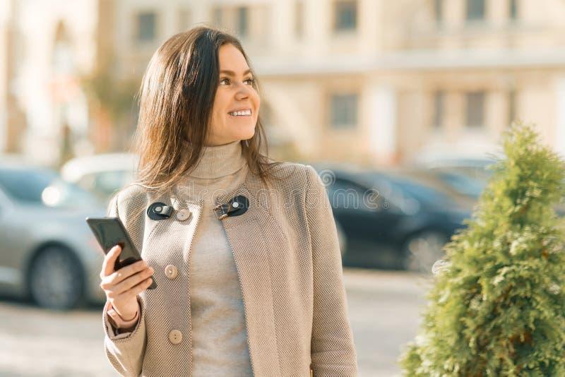 Openluchtportret van een glimlachende gelukkige jonge vrouw met smartphone, de achtergrond van de stadsstraat, de herfst zonnige  royalty-vrije stock foto