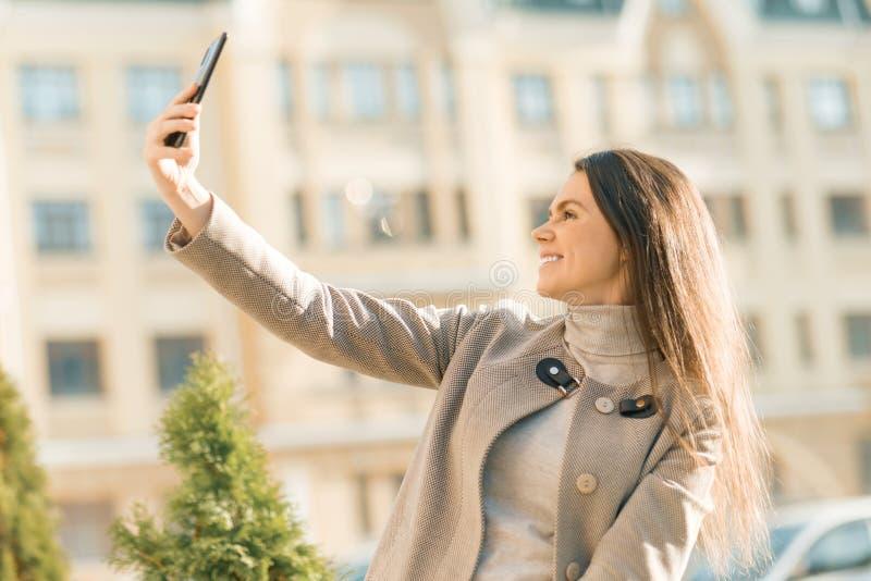Openluchtportret van een glimlachende gelukkige jonge vrouw met smartphone, de achtergrond van de stadsstraat, de herfst zonnige  royalty-vrije stock afbeelding