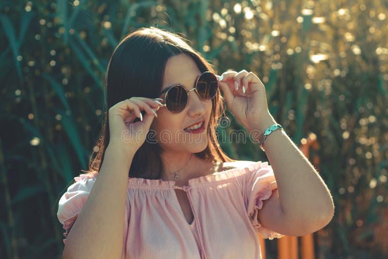 Openluchtportret van een jong meisje dat terwijl greep haar zonnebril glimlacht stock afbeelding