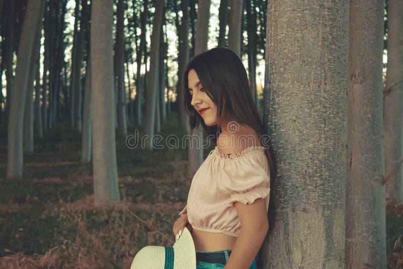 Openluchtportret van een jong meisje die op een boom op ontspannen manier leunen royalty-vrije stock afbeelding