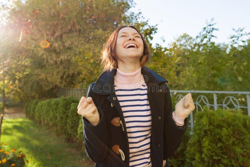 Openluchtportret van een jong tienermeisje met een emotie van geluk, succes, overwinning, gouden uur stock afbeelding