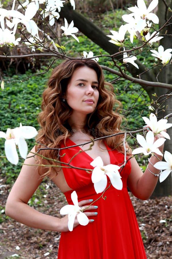 Openluchtportret van een jonge mooie vrouw dichtbij magnoliaboom met bloemen Meisje die modieuze kleren dragen royalty-vrije stock fotografie