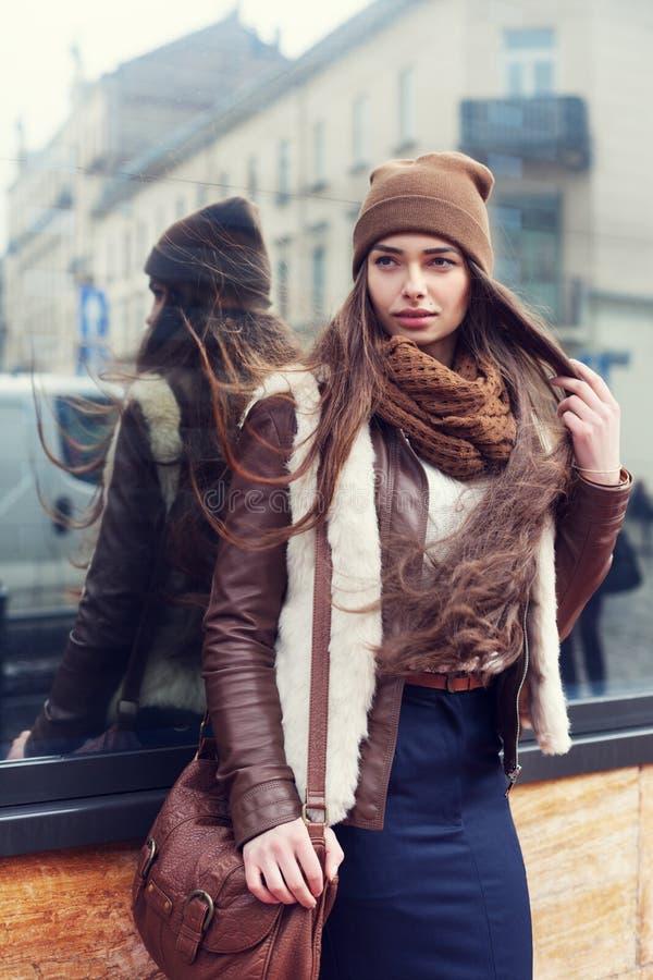 Openluchtportret van een jonge mooie vrouw die modieuze kleren dragen die zich op de straat bevinden Het model opzij kijken stock afbeelding