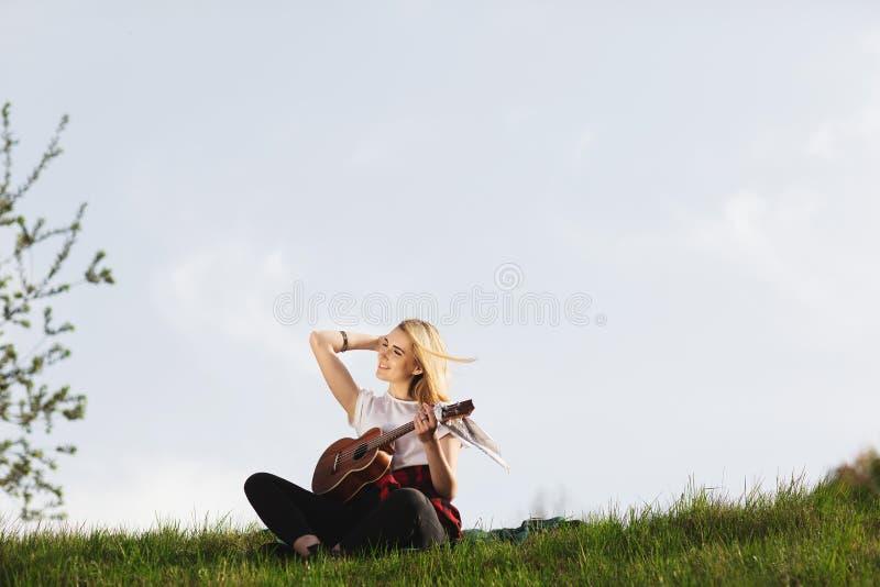 Openluchtportret van een jonge mooie vrouw in zwarte hoed, het spelen gitaar Ruimte voor tekst stock fotografie