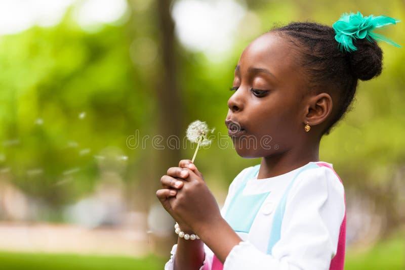 Openluchtportret van een leuk jong zwart meisje die een paardebloem blazen stock afbeelding