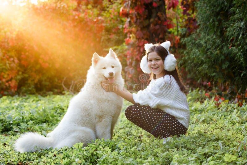 Openluchtportret van een leuk klein kind, een baby of een peutermeisje met haar ter plaatse binnen hond, een gele zitting van Lab stock foto's