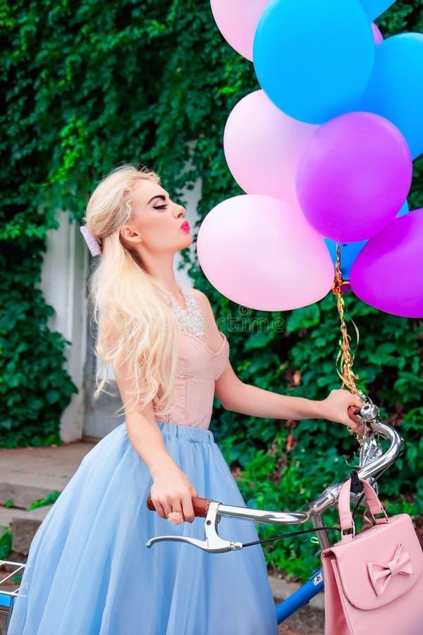 Openluchtportret van een mooi Kaukasisch blondemeisje die heldere ballons en een fiets houden royalty-vrije stock afbeeldingen