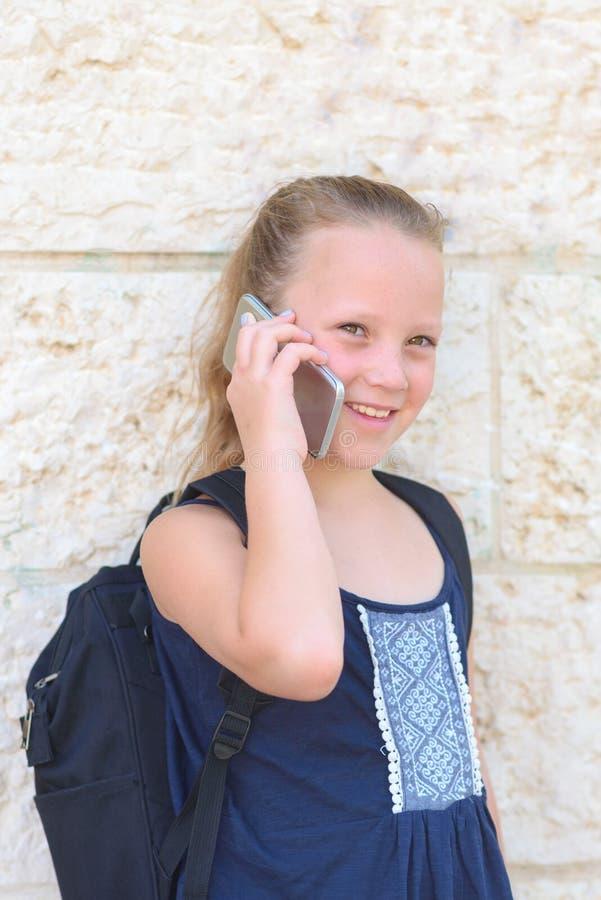 Openluchtportret van gelukkig meisje 8-9 ??njarigen die op telefoon spreken stock afbeelding