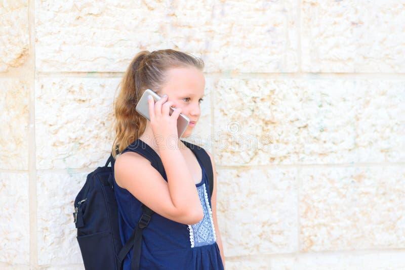 Openluchtportret van gelukkig meisje 8-9 ??njarigen die op telefoon spreken stock afbeeldingen
