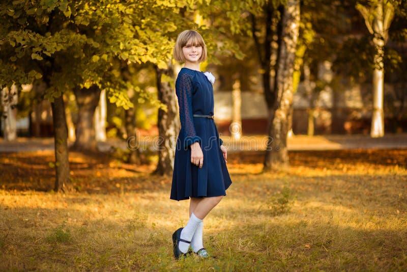 Openluchtportret van gelukkig weinig schoolmeisje in school eenvormig in park Terug naar School stock afbeeldingen