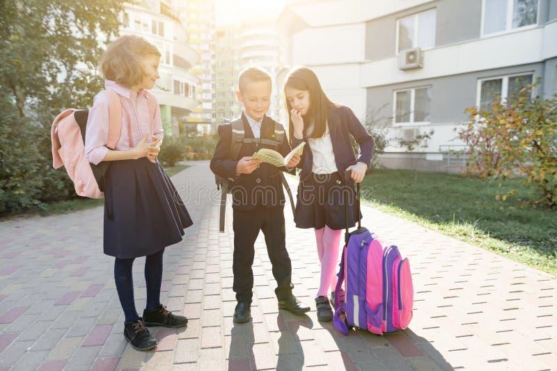 Openluchtportret van glimlachende schoolkinderen in basisschool De groep jonge geitjes met rugzakken heeft pret, spreken, die a l stock afbeelding