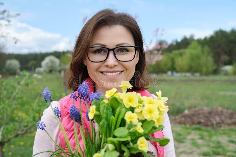 Openluchtportret van glimlachende vrouw op middelbare leeftijd met de lentebloemen in de tuin royalty-vrije stock afbeelding