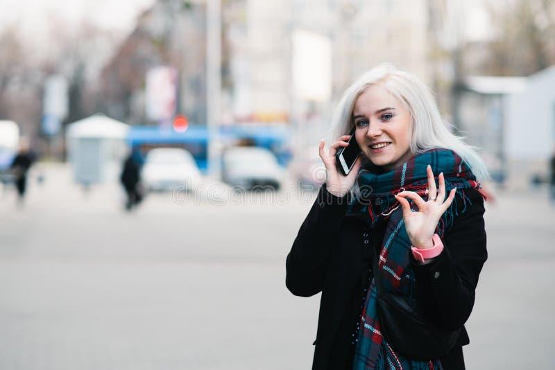 Openluchtportret van het mooie het glimlachen meisje spreken op de telefoon Een jonge vrouw toont teken o.k. royalty-vrije stock afbeelding