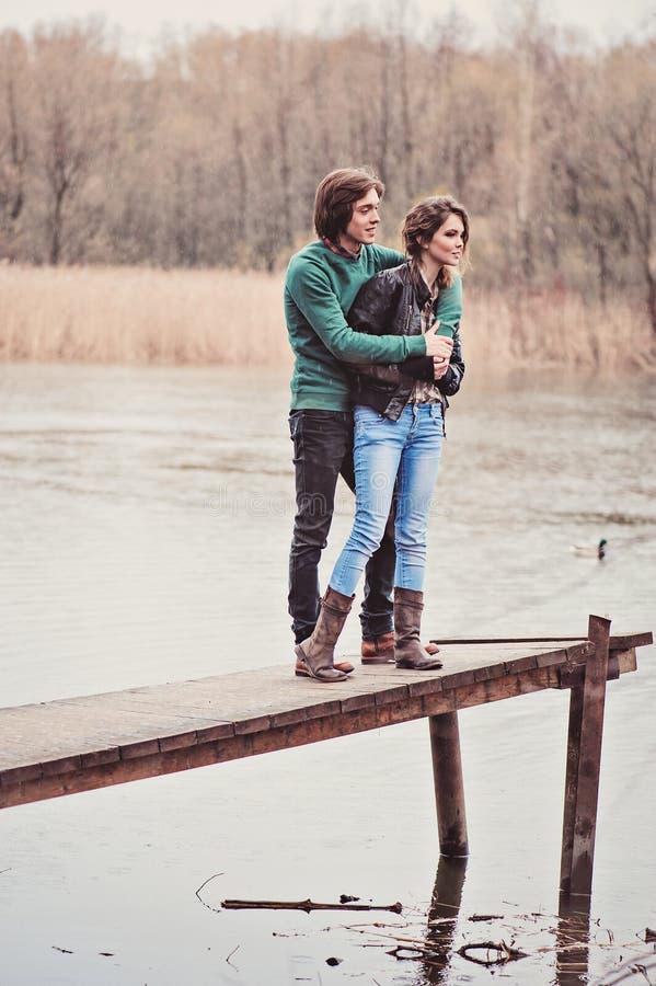 openluchtportret van jong gelukkig houdend van paar die in de vroege lente lopen stock fotografie