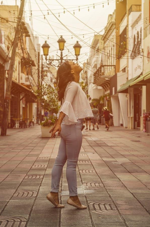Openluchtportret van jong mooi meisje 9 tot 25 jaar het oude stellen in straat het dragen van witte blouse en strakke jeans stock foto