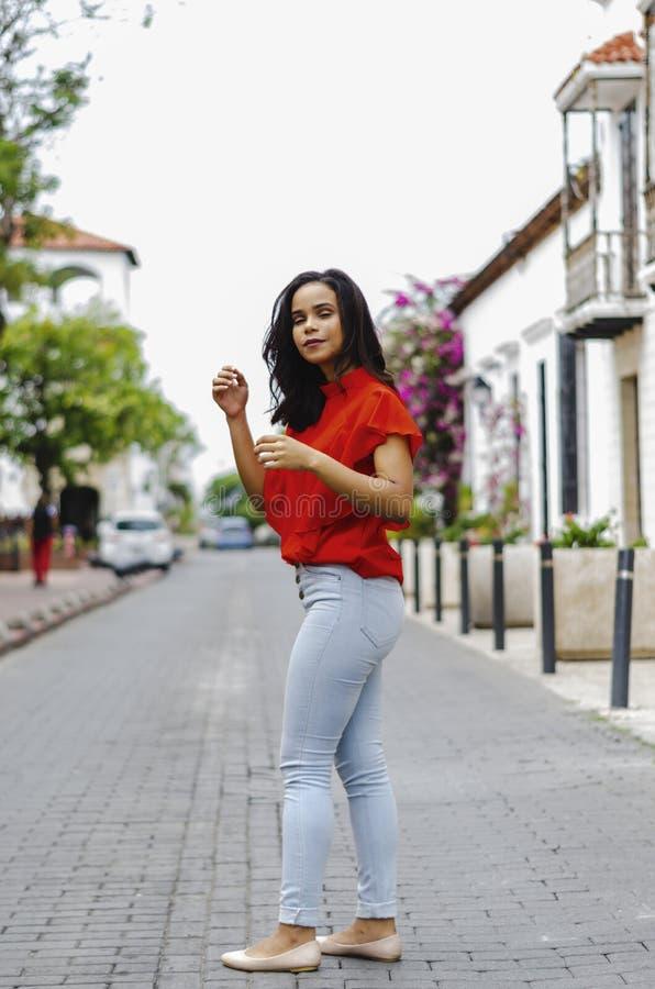 Openluchtportret van jong mooi meisje 19 tot 25 jaar oud Brunette het stellen in het midden van een koloniale straat met keien stock fotografie