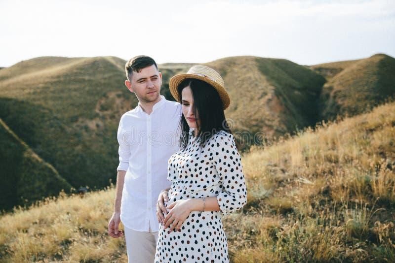 Openluchtportret van jong zwanger paar op gebied stock foto's