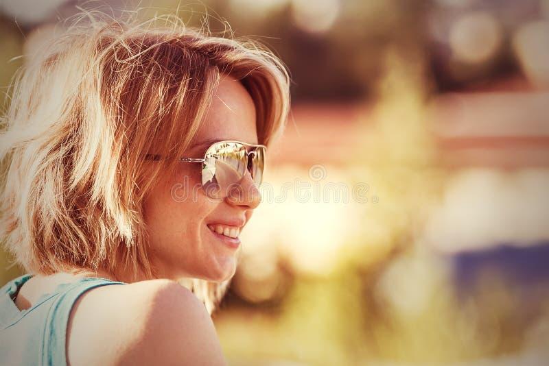 Openluchtportret van jonge glimlachende zonnebrilvrouw stock foto's