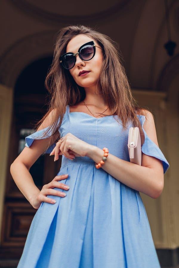 Openluchtportret van jonge mooie vrouw die modieuze zonnebril dragen en beurs houden Manier, schoonheidsmodel royalty-vrije stock afbeelding
