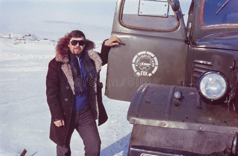 Openluchtportret van jonge sovjetbestuurder dichtbij zijn vrachtwagen royalty-vrije stock afbeelding