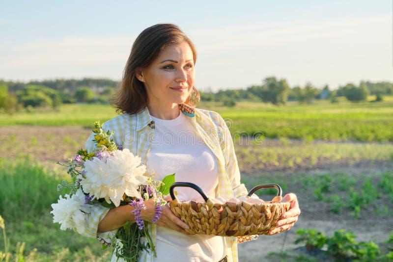 Openluchtportret van landbouwersvrouw met mand van verse kippeneieren, landbouwbedrijf royalty-vrije stock fotografie