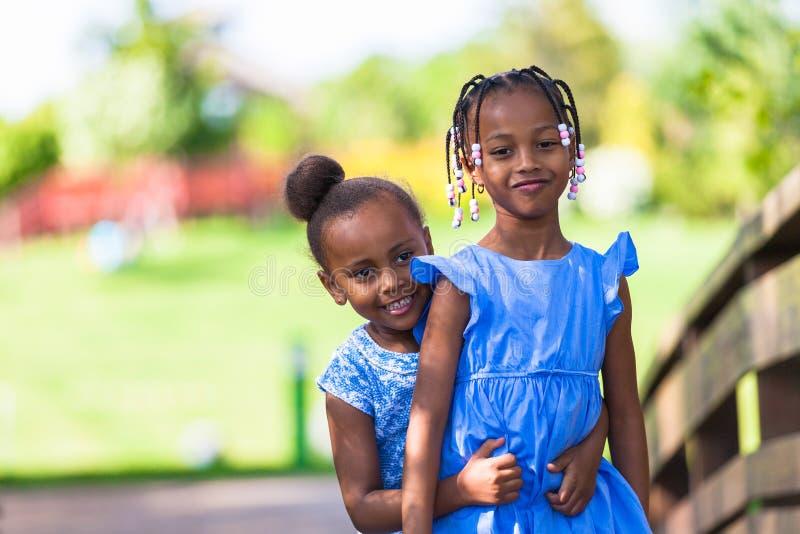 Openluchtportret van leuke jonge zwarte zusters - Afrikaanse mensen royalty-vrije stock afbeeldingen