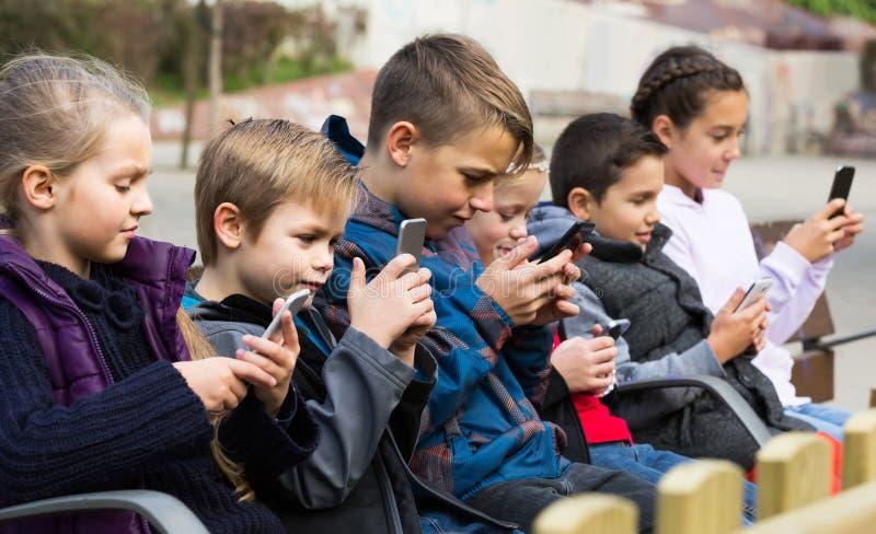 Openluchtportret van meisjes en jongens die met telefoons spelen royalty-vrije stock afbeelding