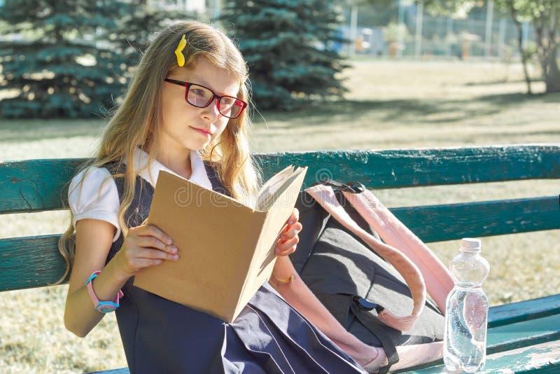 Openluchtportret van mooi meisje in school eenvormige glazen, met rugzakfles die water, boek lezen royalty-vrije stock foto's