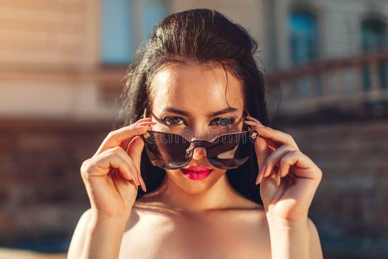 Openluchtportret van mooie donkerbruine vrouw die met samenstelling zonnebril dragen Topless mannequin die glazen weg nemen stock foto's