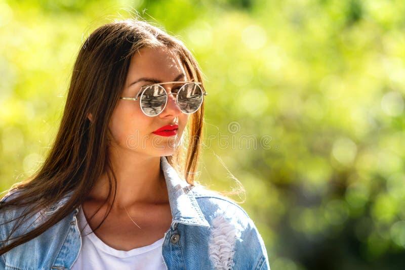 Openluchtportret van mooie, emotionele, jonge vrouw in zonnebril Zachte Achtergrond De ruimte van het exemplaar royalty-vrije stock afbeelding