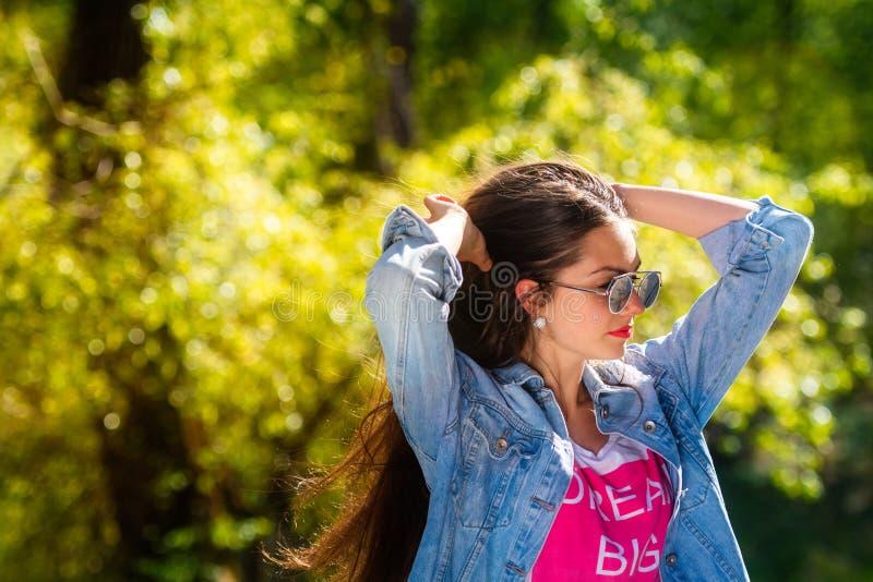 Openluchtportret van mooie, emotionele, jonge vrouw in zonnebril Zachte Achtergrond De ruimte van het exemplaar stock afbeelding