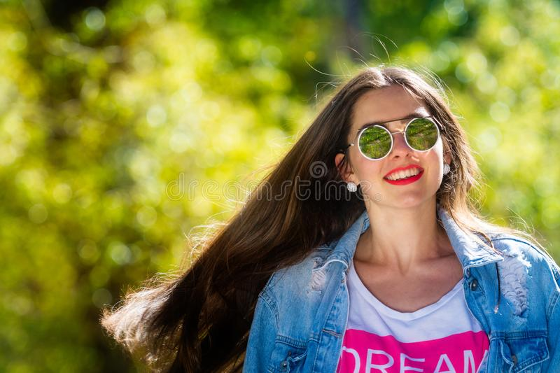 Openluchtportret van mooie, emotionele, jonge vrouw in zonnebril Zachte Achtergrond De ruimte van het exemplaar stock foto