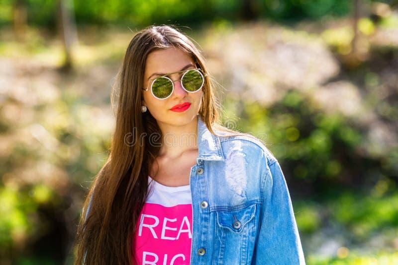 Openluchtportret van mooie, emotionele, jonge vrouw in zonnebril Zachte Achtergrond De ruimte van het exemplaar stock foto's