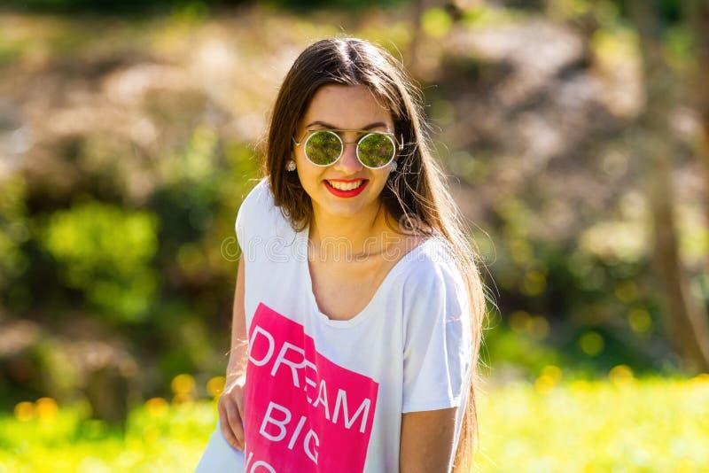 Openluchtportret van mooie, emotionele, jonge vrouw in zonnebril Zachte Achtergrond De ruimte van het exemplaar stock fotografie