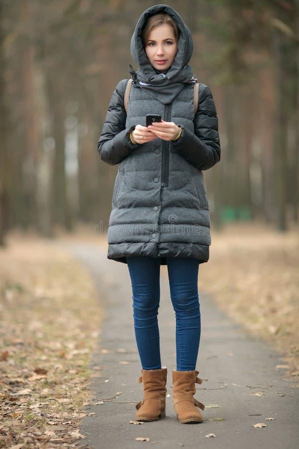 Openluchtportret van mooie nadenkende jonge vrouw die laag met kap het texting bij haar smartphone het stellen in bos de lentepar royalty-vrije stock fotografie