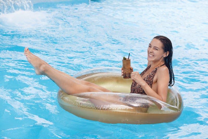 Openluchtportret van mooie vrouw op vakantie, dragend zwemmend kostuum, ontspannend en hebbend pret bij poolpartij Het maken van  stock afbeeldingen