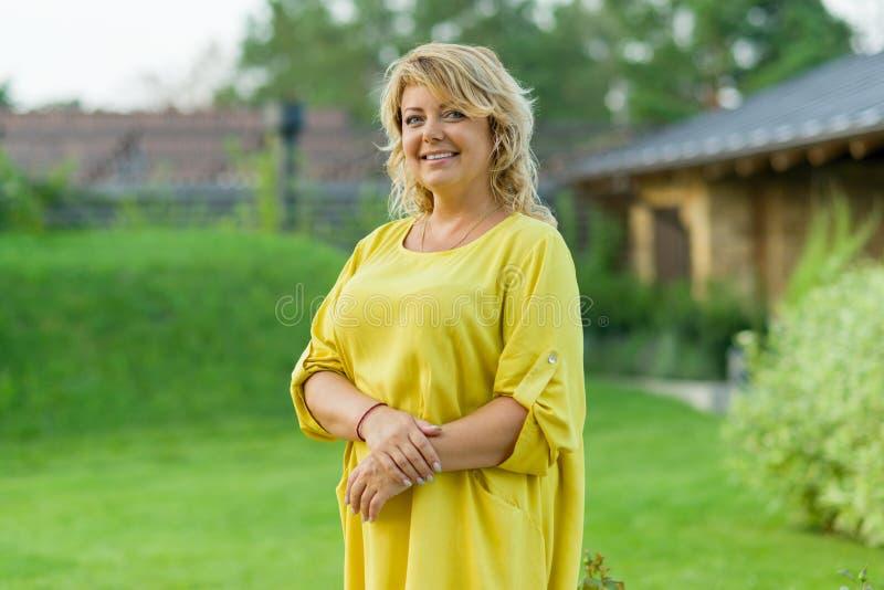 Openluchtportret van positieve rijpe vrouw op middelbare leeftijd, het vrouwelijke glimlachen, achtergrondtuin stock foto
