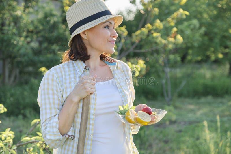 Openluchtportret van positieve rijpe vrouw in strohoed Glimlachend wijfje met plaat van de citroen van de aardbeienmunt, groene a royalty-vrije stock foto