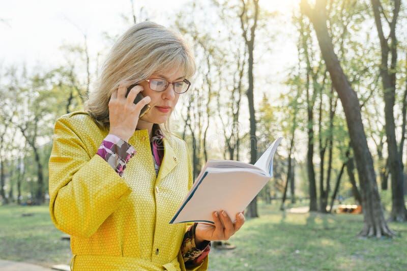 Openluchtportret van rijpe bedrijfsvrouw die met glazen boek lezen die op de telefoon spreken Vrouwelijk blonde in gele regenjas, royalty-vrije stock fotografie
