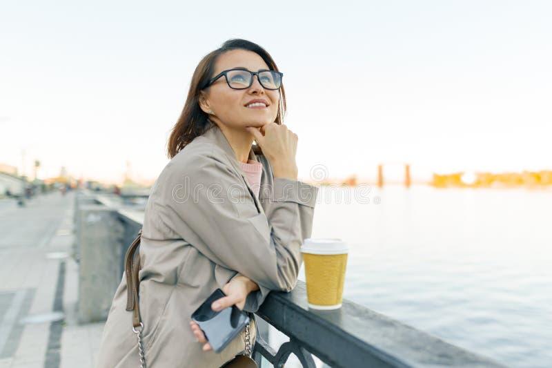 Openluchtportret van rijpe glimlachende vrouw in glazen met kop van koffie en mobiele telefoon Vrouw in de stad op de dijk van stock fotografie