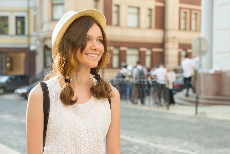 Openluchtportret van tiener 13, 14 jaar oud, de achtergrond van de stadsstraat Het romantische glimlachende mooie meisje in een h royalty-vrije stock afbeeldingen