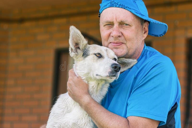 Openluchtportret van twee gelukkige vrienden - rijpe mens en zijn mooie jonge hond stock afbeeldingen