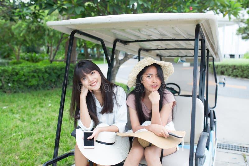 Openluchtportret van twee jonge Aziatische vrouwen die op golfkar zitten royalty-vrije stock afbeelding