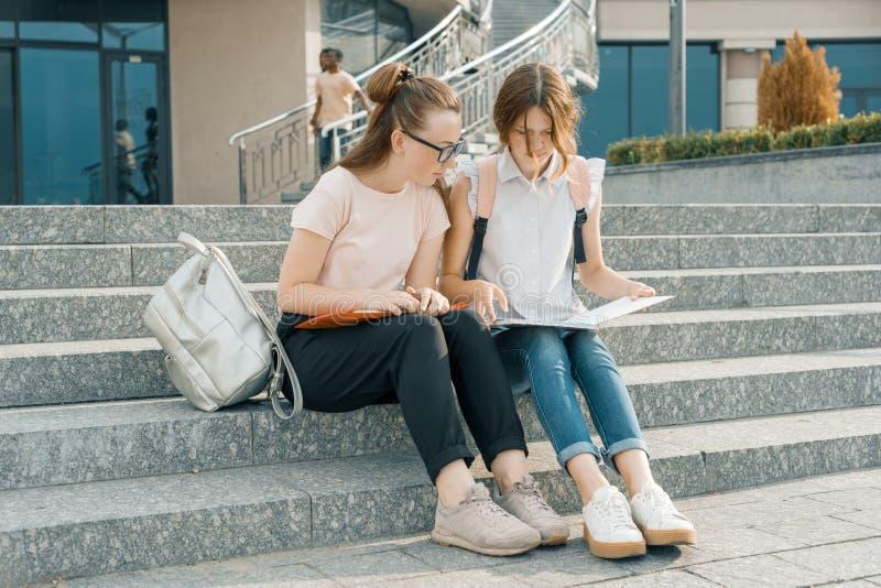 Openluchtportret van twee jonge mooie studentes met rugzakken, boeken Meisjes die op de stappen, het spreken zitten, die a onderz stock afbeelding