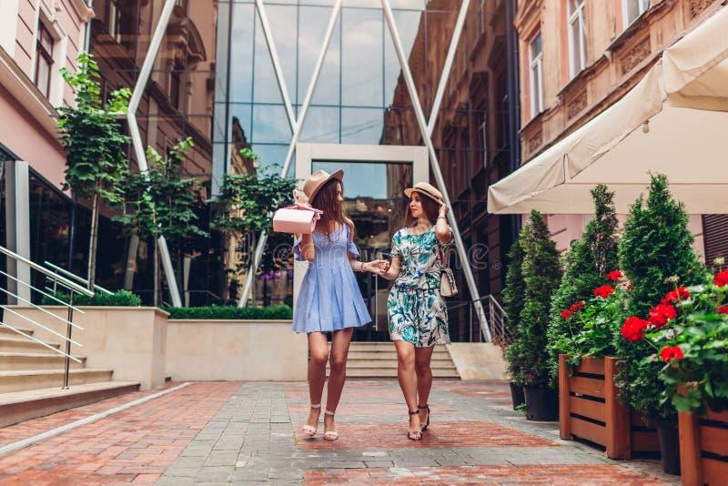 Openluchtportret van twee jonge mooie vrouwen die op stadsstraat lopen Beste vrienden die, hebbend pret hangen royalty-vrije stock foto's