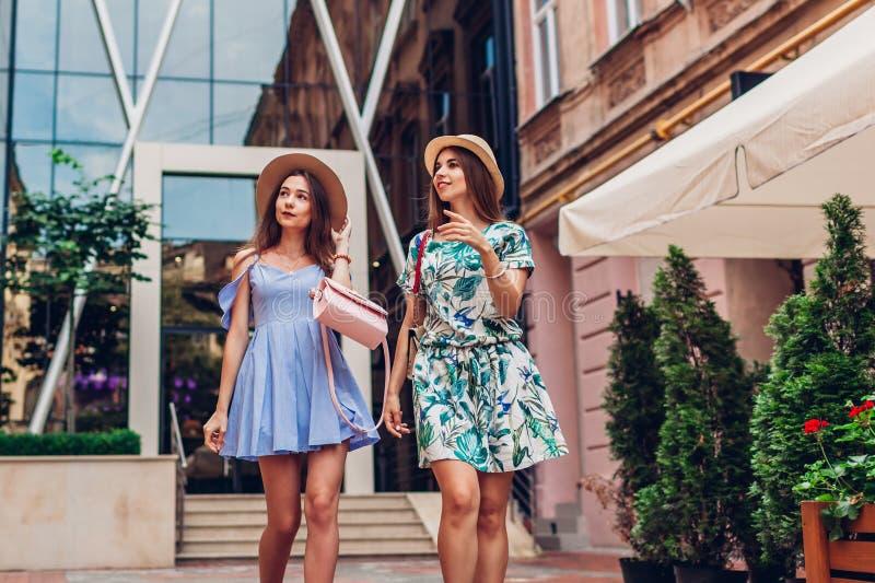 Openluchtportret van twee jonge mooie vrouwen die op stadsstraat lopen Beste vrienden die, hebbend pret hangen stock afbeeldingen