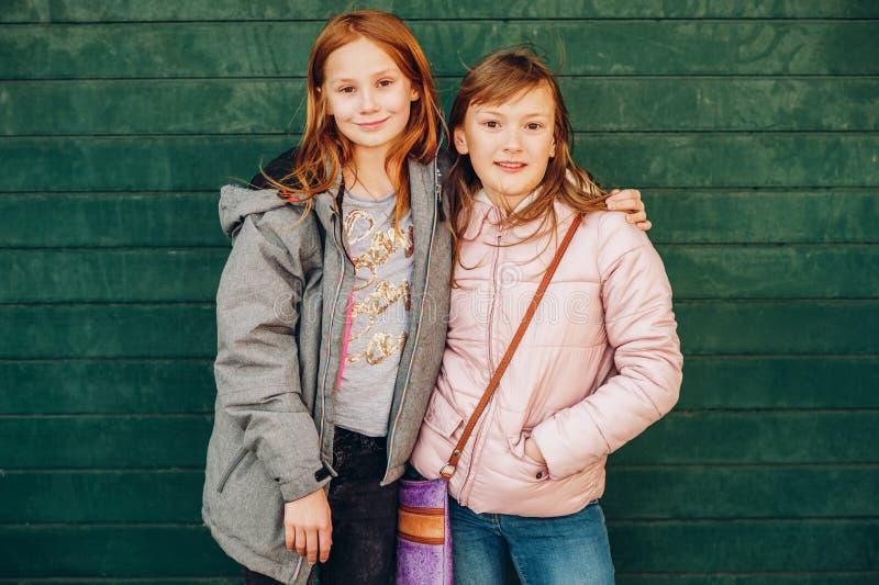 Openluchtportret van twee leuke kleine tienermeisjes die warme jasjes dragen stock afbeeldingen