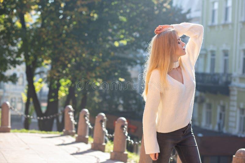 Openluchtportret van verrukkelijk model die het modieuze uitrusting stellen dragen bij de straat met natuurlijk zonlicht Lege rui royalty-vrije stock afbeelding