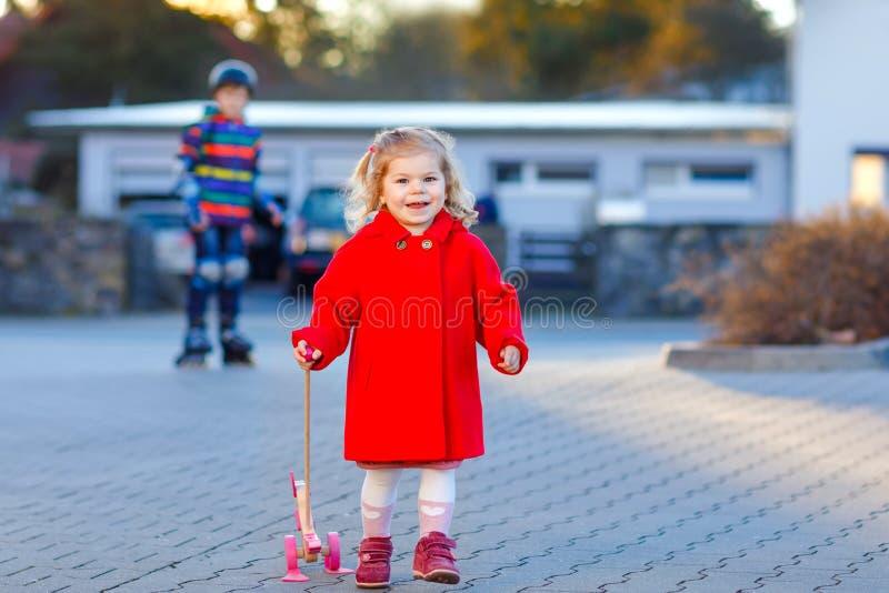 Openluchtportret van weinig leuk peutermeisje in rode de lente zonnige dag van laagaon met duw houten stuk speelgoed Gezonde gelu royalty-vrije stock foto's
